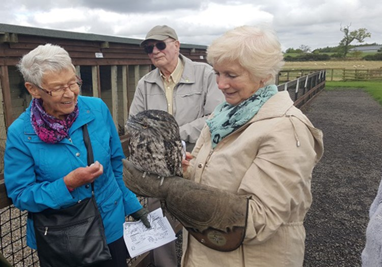 Older woman holding owl
